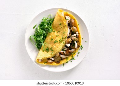 Omelette stuffed with mushrooms, pieces of chicken meat, greens on white stone background. Top view, flat lay