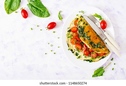 Omelette with tomatoes, spinach and green onion on white plate.  Frittata - italian omelet. Top view. Flat lay.