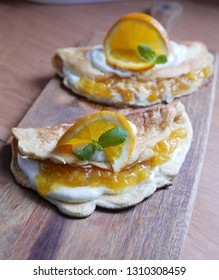 Omelettes with peach sauce and homogenized cheese, slices of orange with mint leafs, served on a wooden cutting table