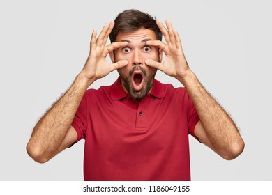 Omg concept. Stunned emotive bearded European guy with eyes popped out, drops jaw, keeps hands on face, dressed casually, poses against white background. People, reaction and amazement concept