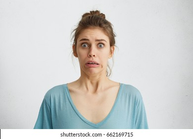 Omg! Cropped shot of frightened terrified woman with blue popped out eyes frowning her lips with panic. Moving stressful woman in blue shirt realizing horrified news looking with anxiety into camera