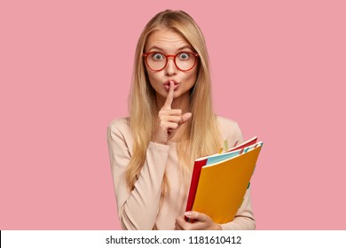 Omg, dont speak! Attractive Caucasian girl keeps index finger over lips, demonstrates silence gesture, asks not bother her, be quiet and speechless, wears spectacles with red rim isolated on pink wall