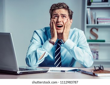 OMG! Frustrated man sitting desperate over paperwork at desk. Modern businessman at the workplace, depression and crisis concept