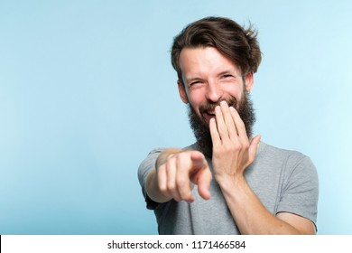 omg. ha-ha. bearded hipster man mocking and laughing at viewer pointing finger and covering mouth. sneer humiliation and psycological abuse concept. portrait of a grinning guy on blue background.