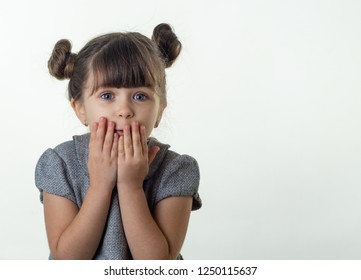 OMG! Happy surprised child 4 or 5 years old isolated on white. Oh no! Terrified shocked child with bugged eyes covers mouth with hands. Copy space.