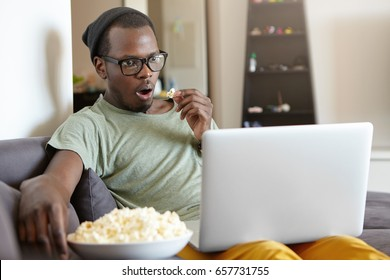 Omg! Hipster African young man in stylish clothes looking emotional being fascinated by blockbuster. Amused dark-skinned man watching films at home using his laptop and free wi-fi conncetion
