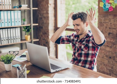 Wtf?! Omg! Oh no! Young amazed emotional brunet with bristle with sad grimace looks at screen of device, he can`t believe the bad news he received, sitting at workstation, gesturing with palms of arms