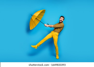 Omg parasol flying. Full size photo of crazy astonished man catch his rain wind protect shield umbrella scream wear plaid pants sneakers isolated over blue shine color background