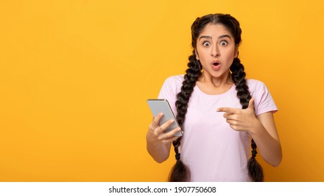Omg. Portrait Of Emotional Shocked Indian Lady Holding And Using Mobile Phone, Pointing At Device. Surprised Woman Standing With Smartphone Isolated Over Yellow Studio Background, Banner, Copy Space