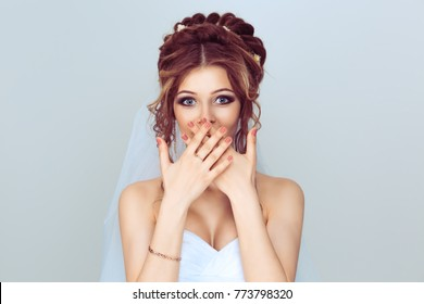 OMG. Pretty beautiful excited surprised woman bride girl covering her open mouth with hands, over light blue background. Positive face expression