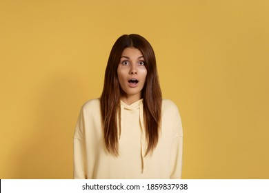 omg. Stunned friendly caucasian woman in yellow hoodie, keeps jaw dropped, opens eyes widely, cant believe in fortune, expresses great surprisement. Isolated over a yellow background