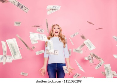 Omg, wow! Portrait of funny impressed girl with unexpected unbelievable reaction standing under shower from hundred 100 dollars, flying money isolated on pink background