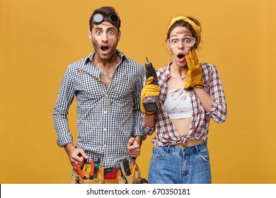 Omg! Wow! Studio portrait of emotional surprised young European service technicians wearing safety goggles looking at camera in full disbelief, keeping mouths wide opened and eyes popped out