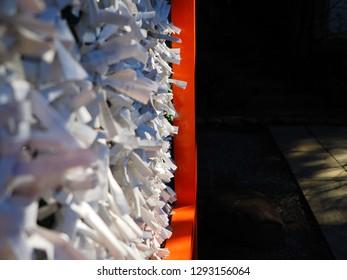 Omikuji, small strips of paper with fortunes or prayers written on them, tied onto wires