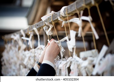 'Omikuji' at Yasaka Shrine, Japan. Omikuji is fortune telling paper strip. People leave the omikuji behind if it's not a good one.