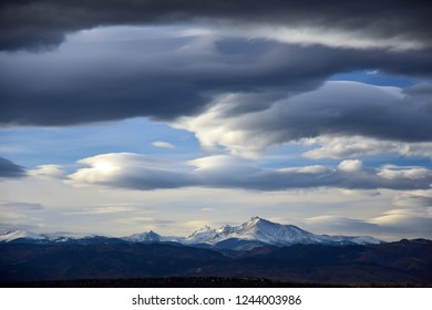 ominous afternoon storm clouds over long's peak and the front range of the colorado rocky mountains, as seen from broomfield, colorado