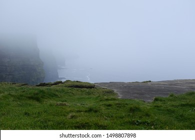 Ominous Atmospheric Overcast Foggy  Cliff Mountain Edge with Green Grass and Sandy Rocky Ground Overlooking Drop and Blue Grey Ocean Sea