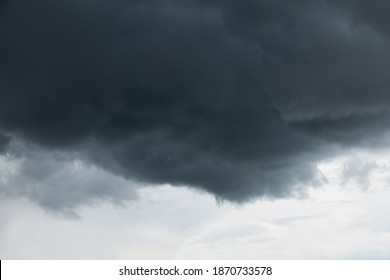 Ominous cloud overhead. Impending black rain cloud on light gloomy sky. Nature Dramatic Sky Background, texture for Design. Artistic Wallpaper or Web banner With Copy Space