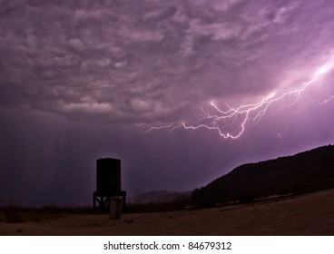 Ominous clouds as lightning creeps toward an abandoned water tower at Dos Cabezas Siding in the Anza-Borrego Desert. San Diego County.