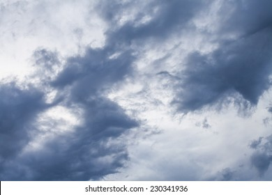 Ominous dark grey and blue wispy fractus storm clouds during a high wind contrasted against a lighter color sky