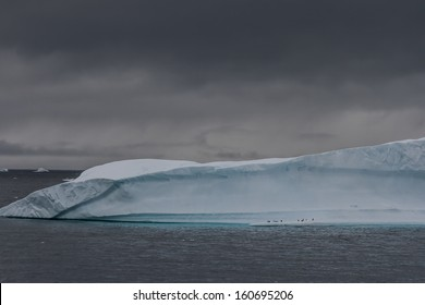 Ominous iceberg with penguins near Useful Island, Antarctica