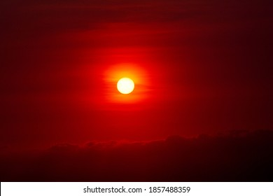 Ominous red sun setting over clouds red sky with dark edges
