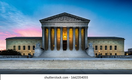 Ominous shadows on the front of illuminated United States Supreme Court building in Washington DC with sunrise clouds and sky in background and marble steps in foreground.