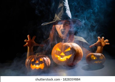 An ominous witch in a hat conjures over a jack-o-lantern. Traditional halloween characters. Mystical fog creeps over pumpkins with carved terrible faces. An evil witch casts a spell.