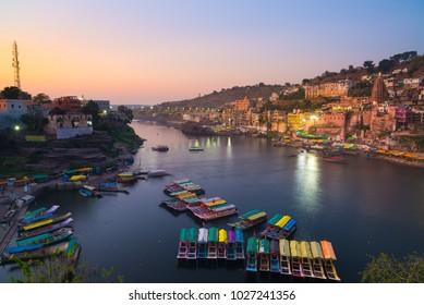 Omkareshwar cityscape at dusk, India, sacred hindu temple. Holy Narmada River, boats floating. Travel destination for tourists and pilgrims.