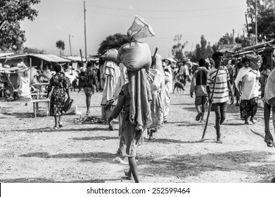 OMO, ETHIOPIA - SEPTEMBER 19, 2011: Unidentified Ethiopian women walk with bags on the heads. People in Ethiopia suffer of poverty due to the unstable situation