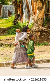 OMO, ETHIOPIA - SEPTEMBER 21, 2011: Unidentified Ethiopian woman carries her little baby on her back. People in Ethiopia suffer of poverty due to the unstable situation