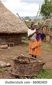 OMO VALLEY, ETHIOPIA - AUG 10: Derashe woman with her baby in the village, the ethnic groups in the Omo valley  Could disappear because of Gibe III hydroelectric dam on Aug 10, 2011 in Omo Valley, Ethiopia.