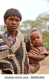 OMO VALLEY, ETHIOPIA - AUG 10: Tsemay woman posing with her baby in the village, the ethnic groups in the Omo valley  could disappear because of Gibe III hydroelectric dam on Aug 10, 2011 in Omo Valley, Ethiopia