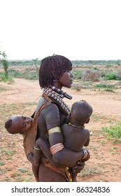 OMO VALLEY, ETHIOPIA - AUG 15: Unidentified Hamer woman with her children, the ethnic groups in the Omo valley could disappear because of Gibe III hydroelectric dam on Aug 15, 2011 in Omo Valley, Ethiopia.