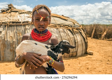 OMO VALLEY, ETHIOPIA - MAY 6, 2015 : Girl from the African tribe Dasanesh holding a goat in her village.