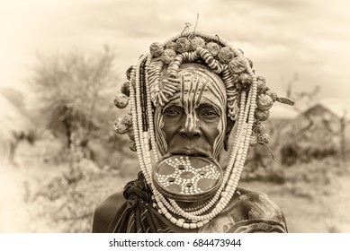OMO VALLEY, ETHIOPIA - MAY 7, 2015 : Woman from the african tribe Mursi with big lip plate in her village. Vintage black and white processed.