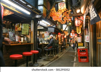 Omoide Yokocho,Shinjuku,Tokyo,Japan-November 2016: A narrow alleys close to the west Exit of Shinjuku Station. Tired Tokyo office workers relax with a beer and barbecue food at night.