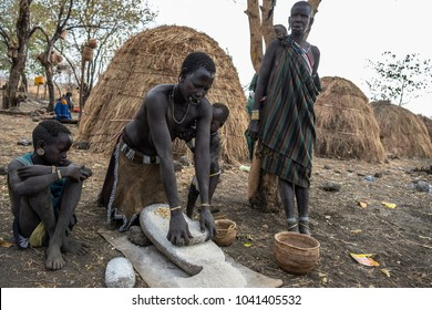 OMORATE, ETHIOPIA - JANUARY 24: Unidentified women from Mursi tribe are grinding cereals with a stone to prepare flour with the traditional houses in the background on January 24, 2018 in Ethiopia.