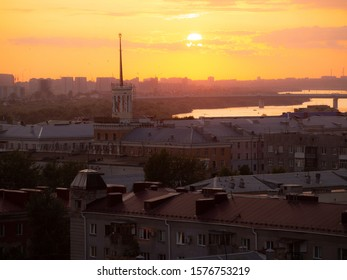 Omsk, Russia - 06.07.2019: Sunset over the city of Omsk. A recognizable symbol of Omsk is visible - a house with a spire. As well as the Om River and the metro bridge of the city of Omsk.