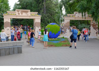 """Omsk, Russia - August 7, 2018: City exhibition of green building, floriculture and gardening """"Flora-2018"""". Entrance to the Exhibition Square. Model of the globe, covered with flowers"""