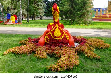 """Omsk, Russia - August 7, 2018: City exhibition of green building, floriculture and gardening """"Flora"""". Exhibition Square. Landscape composition """"Russian folk crafts"""". Swan of flowers and wooden spoons"""