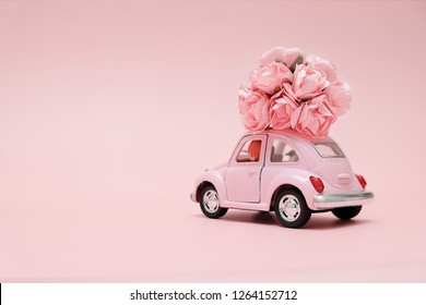 Omsk, Russia - December 20, 2018: Pink retro toy car delivering bouquet of flowers box on pink background. February 14 card, Valentine's day. Flower delivery. 8 March, International Happy Women's Day.