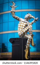 """OMSK, RUSSIA - JULY 31, 2018: A sculpture of the Harlequin sitting on the column, holding a glove doll Petrushka in the hands of the state puppet theater, actor, mask """"Harlequin"""""""