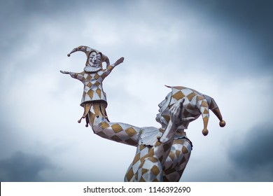"""OMSK, RUSSIA - JULY 31, 2018: Sculpture of Harlequin close-up against the sky that holds the glove doll Petrushka in the hands of the state puppet theater, actor, mask """"Harlequin"""""""