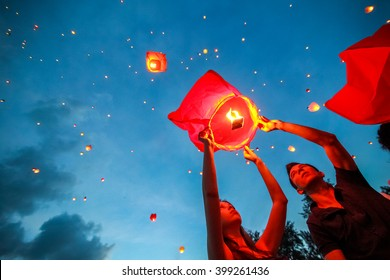Omsk, Russia - June 16, 2012: festival of Chinese paper lantern, the man starts lantern in the sky at night