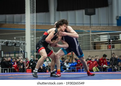 Omsk, Russia – March 01 2021: Championship of Russia in Greco-Roman wrestling among young men. Greco-Roman wrestlers in blue and red tights wrestle in a stall on a blue carpet