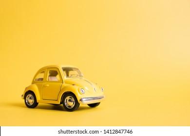 Omsk, Russia - May 26, 2019: Yellow retro toy car on yellow background. Valentine's day. Flower delivery. 8 March, International Happy Women's Day. Summer travel concept. Taxi