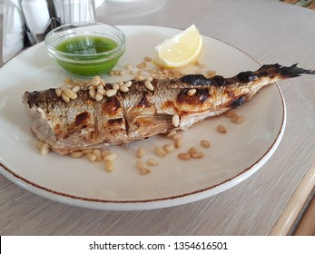 Omul fish steak served with green sauce and lime in white plate on wooden table; Omul fish is local fish and local food of Lake Baikal area in Siberia, Russia. (shoot from mobile camera)