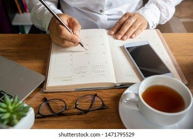On 2020 Calendar and diary book,Female'hand of planner writing daily appointment.Woman mark and noted schedule(holiday trip) on diary at office desk.Calendar reminder event for planner concept