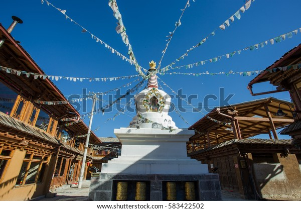 On 6 DEC, 2016. : White Tibetan pagoda and colorful prayer flags. Tradition Chinese building. Located in Guishan park, Old Town of Dukezong, Shangri-La, China.